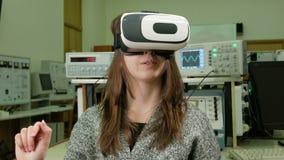 Student för ung kvinna med virtuell verklighetexponeringsglas i det fysiska laboratoriumet av universitetet Hon betraktar modelle arkivfilmer