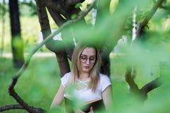 Student för ung kvinna som läser en bokbenägenhet på ett träd i parkera Arkivbild