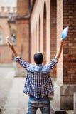 Student för ung man med lyftta händer av framgång framme av Uni universitetsområdet Happuseger för ung man av passerandeexamen St royaltyfri fotografi