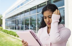 Student failed exam. Stressful girl touching her and holding tablet outside Stock Images