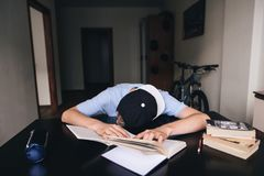 The student fell asleep doing homework at books and notebooks in his room. Teaching at home. Sleep at the table Royalty Free Stock Photos