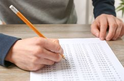 Student filling answer sheet at table. Closeup royalty free stock photography