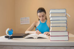 Student flicka som hemma studerar med många böcker Royaltyfria Foton