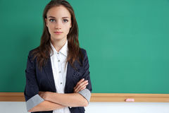 Student folded arms near blackboard. Stock Photography