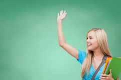 Student with folders waving hand over school board Royalty Free Stock Image