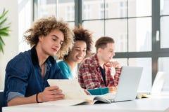 Student framme av en bok, medan sitta ner på skrivbordet Arkivbild