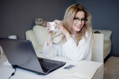 Student or freelancer, working at home with laptop. Charming young woman sits in front of monitor with Cup of coffee. Student or freelancer, working at home royalty free stock image