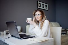 Student or freelancer, working at home with laptop. Charming young woman sits in front of monitor with Cup of coffee. Stock Image