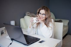 Student or freelancer, working at home with laptop. Charming young woman sits in front of monitor with Cup of coffee. Royalty Free Stock Photos