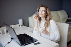 Student or freelancer, working at home with laptop. Charming young woman sits in front of monitor with Cup of coffee. Royalty Free Stock Photo