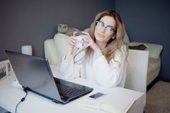 Student or freelancer, working at home with laptop. Charming young woman sits in front of monitor with Cup of coffee. Stock Images