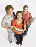 Student friends carrying bags and books. Three students smiling up at the camera while posing with their school books Stock Image