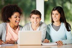 Student With Friends Looking bij Laptop binnen Stock Fotografie