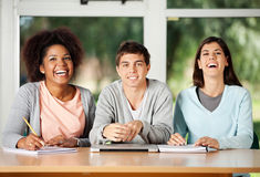Student With Friends Sitting At Desk In Classroom. Portrait of young male student with friends sitting at desk in classroom Royalty Free Stock Images
