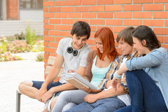 Student friends studying together outside campus Stock Image