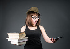 Student in funny glasses with old books in one hand and e-reader in another on grey background. Nerd girl is comparing Royalty Free Stock Image