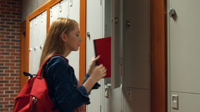 Student gathering her school books from a locker. In the university college stock video footage