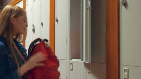Student gathering her school books from a locker stock footage