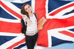 Student Gesturing Thumb Up Sign. Young Female Student Gesturing Thumb Up In Front Of British Flag stock photo