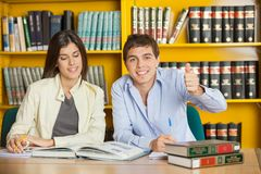 Student Gesturing Thumbsup While Friend Reading. Portrait of happy male student gesturing thumbsup while friend reading book at table in college library Royalty Free Stock Photo