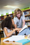 Student getting help from classmate in library Royalty Free Stock Photography