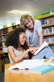 Student getting help from classmate in library Stock Images