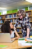 Student getting help from classmate in library Royalty Free Stock Photos
