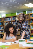Student getting help from classmate in library Stock Photos