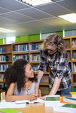 Student getting help from classmate in library Royalty Free Stock Photo
