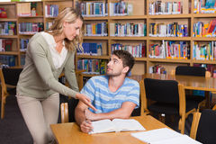 Student getting help from tutor in library Royalty Free Stock Photos
