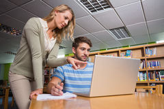 Student getting help from tutor in library Stock Photography