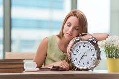The student with gian alarm clock preparing for exams Stock Photos