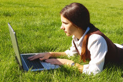 Student girl. Young beautiful woman, lying on the grass with the laptop Royalty Free Stock Images