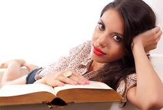 Student girl. Teenage girl sitting on the couch reading a book Royalty Free Stock Images
