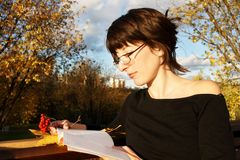 Student girl with ashberries. Beautiful brunette in glasses reading book in autumn park Stock Images
