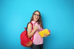 Student girl with backpack and books. Portrait of student girl with backpack and books on blue background stock photo