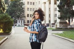 Student girl with backpack and mobile at university building background. Happy african-american student girl talking on mobile at university background. Woman Stock Image