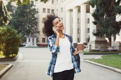 Student girl with backpack and mobile at university building background. Happy african-american student girl talking on mobile at university background. Woman Stock Photos