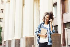 Student girl with backpack and mobile at university building background. Happy african-american student girl talking on mobile at university background. Woman Stock Photo
