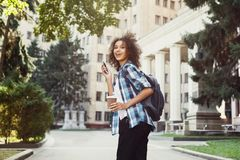 Student girl with backpack and mobile at university building background. Happy smiling african-american student girl with backpack at university background Royalty Free Stock Images