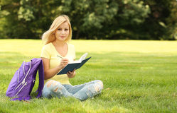 Student girl with book and backpack in park. Blonde young woman Stock Images