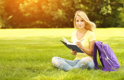 Student girl with book and backpack in park royalty free stock image