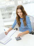Student girl with book, calculator and notebook Stock Photos