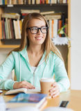 Student girl with book drinking coffee in library Royalty Free Stock Image