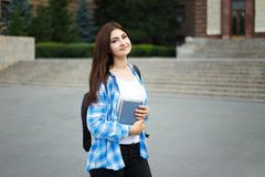 Student girl with books and backpack standing near university bu. Ilding. Campus life, education concept royalty free stock image