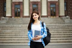 Student girl with books and backpack standing near university bu. Ilding. Campus life, education concept royalty free stock photography