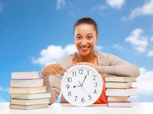 Student girl with books showing time on clock royalty free stock photography