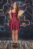 Student girl with books stands in front of class blackboard Royalty Free Stock Images