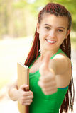 Student girl with braids and thumb up. Cheerful student girl with ethnic hairstyle and thumb up, outside, focus on face Stock Image