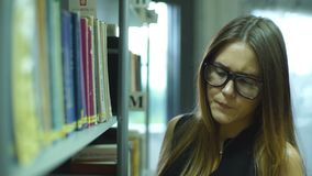 Student girl chooses among the shelves of a book in the library stock video
